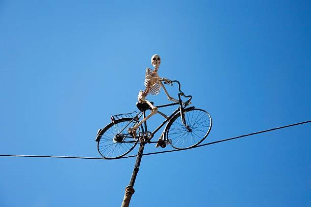 Imagen que contiene azul, esqueleto,bicicleta, sobre un cable